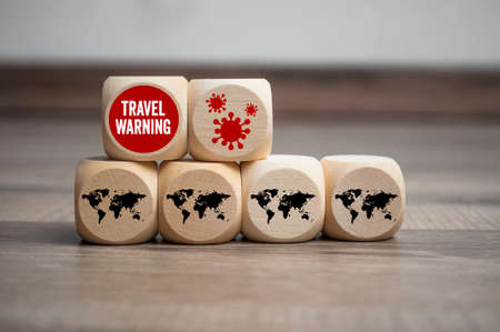 Cubes and dice with covid-19 corona virus and travel warning on wooden background Archivio Fotografico