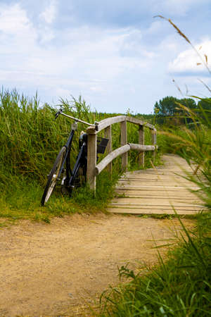 Old bike standing at a wooden boardwalk at the coast in germany baltic sea Stock Photo