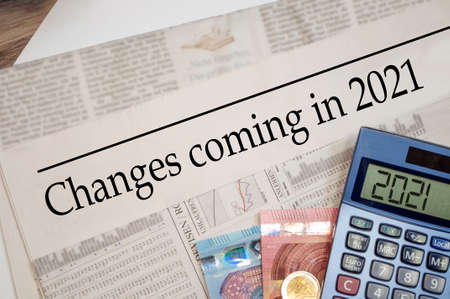 Newspaper with money and calculator and headline Changes coming in 2021 Foto de archivo