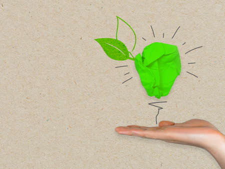 Green paper light bulb metaphor for recycling and green renewable energy green climate concept on brown recycled paper