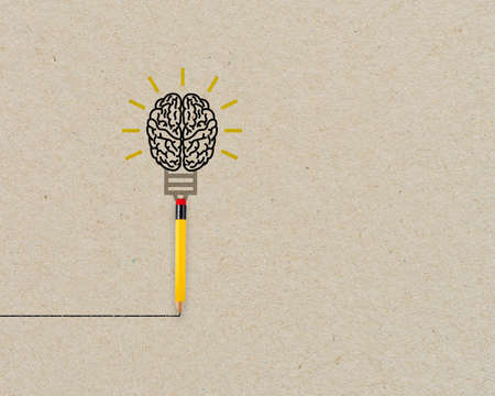 Yellow pencil with brain and light bulb metaphor for creative and new idea on brown recycled background