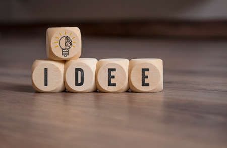Cubes, dice and blocks with a brain and light bulb showing the word Idea and Idee on wooden background