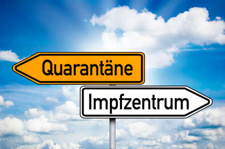 Road sign with the German words for covid-19 vaccination center or center and quarantine - Quarantäne und Impfzentrum with blue sky background 版權商用圖片