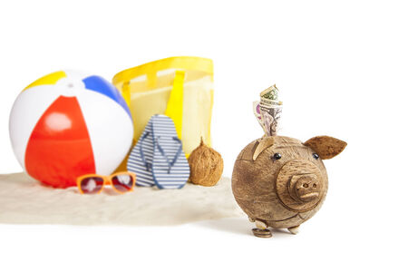 Coconut Piggy bank in foreground with Colorful Beach Ball, Star Fish and Sandals, Flip Flops in Beach Sand in background on isolated white