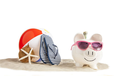 White ceramic Piggy bank in foreground with Colorful Beach Ball, Star Fish and Sandals, Flip Flops in Beach Sand in background on isolated white photo