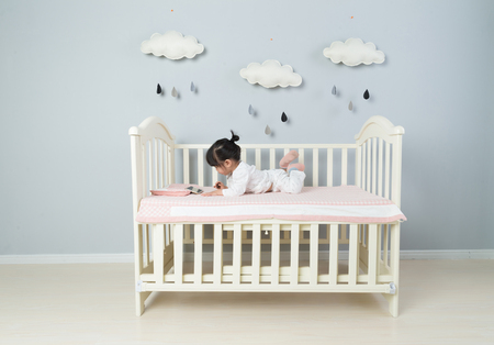 Beautiful little girl sits on white blanket in her bedroom Stock fotó