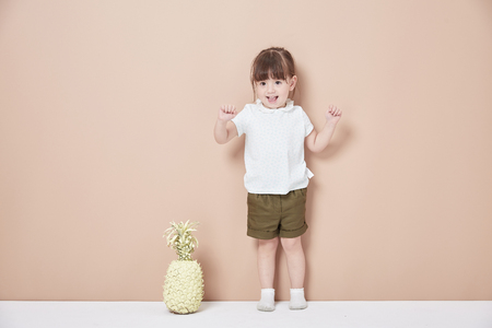 The happy little girl showed a naughty look in front of the background wall Reklamní fotografie