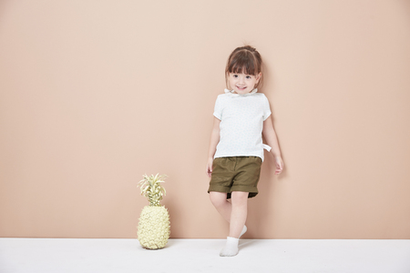 The happy little girl showed a naughty look in front of the background wall Stock fotó