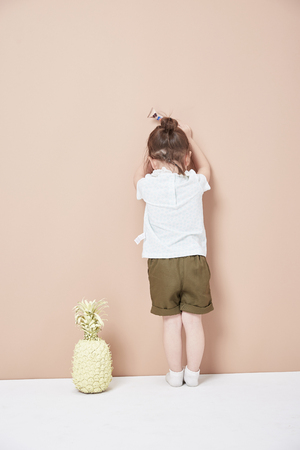 The little girl's back, round head, a thin braid in her hair. Stock Photo