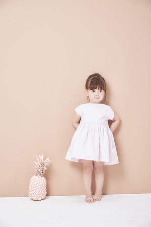 The little girl stood in front of the wall in a white dress, lively and lovely.