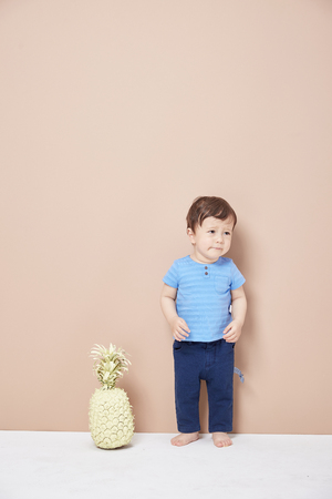 A cute, cheerful little boy who just learned to walk, wearing jeans T-shirt.