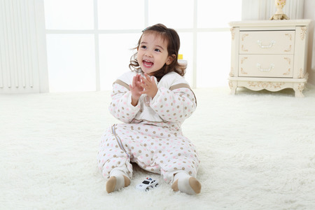 the pretty little girl was sitting on the carpet playing in her warm pajamas Stock Photo