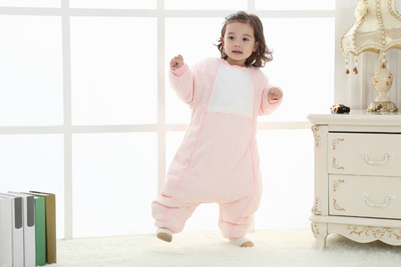 the happy little girl jumps in the room wearing a baby bear sleeping bag