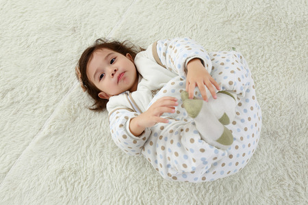 the sweet little girl was lying on the white carpet in her wars pajamas