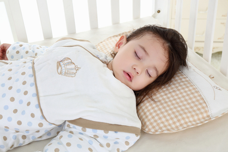 the sweet little girl sleeping in the pink cradle with blur in the foreground Stock fotó