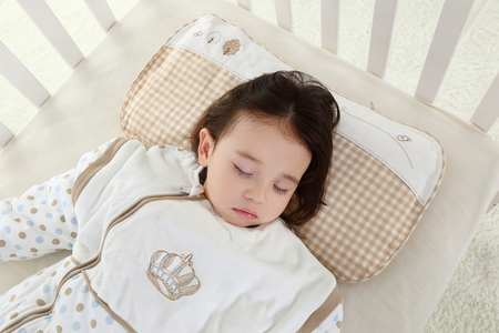 the sweet little girl sleeping in the pink cradle with blur in the foreground Stock Photo