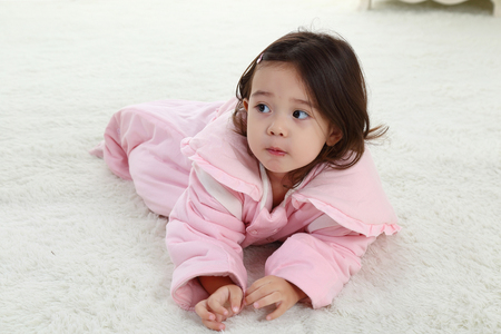 the sweet little girl was playing in her bedroom in pink pajamas Stock Photo