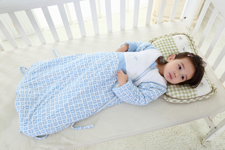 the happy little girl was lying on her cot in a warm sleeping bag Stock Photo