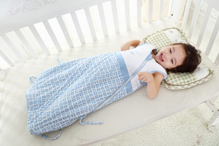 the happy little girl was lying on her cot in a warm sleeping bag Stockfoto