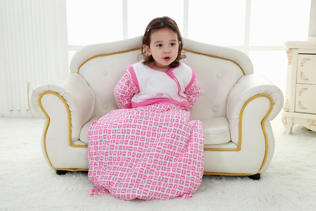 A beautiful girl, a child on a chair in a nice dress Stock Photo