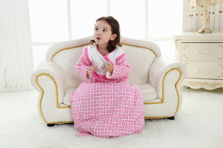 A beautiful girl, a child on a chair in a nice dress Stock fotó