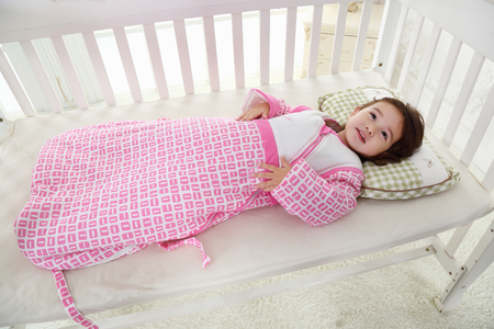 the happy little girl was lying on her cot in a warm sleeping bag Stock fotó