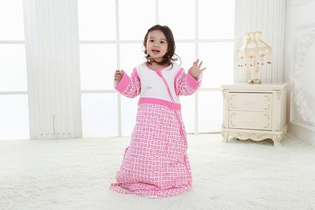 the happy little girl is wearing a sleeping bag portrait