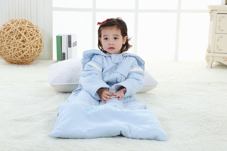 A little girl was sitting on the bed in her sleeping bag Stock Photo