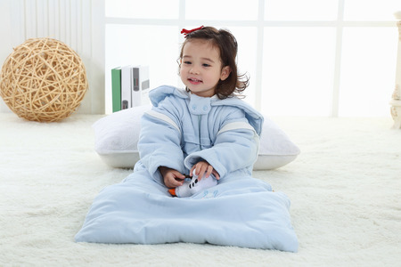 A little girl was sitting on the bed in her sleeping bag Stock fotó
