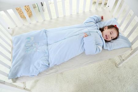 beautiful little girl lying in bed in her sleeping bag Stock Photo