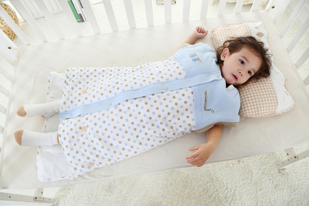 the little girl was lying in bed in her sleeping bag Stock Photo