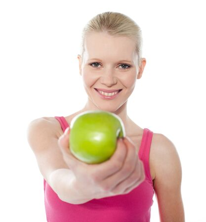 Teenager offering green apple, full of vitamins isolated on white Stock Photo - 13217132