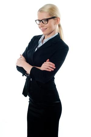 Zijaanzicht van mooie jonge vrouwelijke executive poseren met armen gekruist