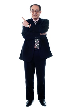 Smiling old businessperson pointing up isolated on white background photo