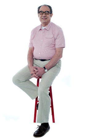 Confident senior man looking at you as he rests on stool, studio shot photo