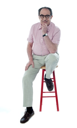 stool: Confident senior man looking at you as he rests on stool, studio shot