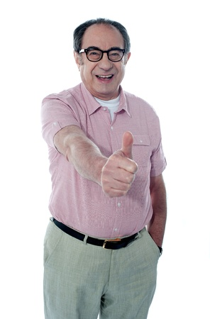 Smiling aged male gesturing thumbs-up, portrait photo