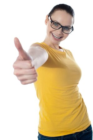 Pretty teenager showing thumbs-up wearing glasses Stock Photo - 13217423