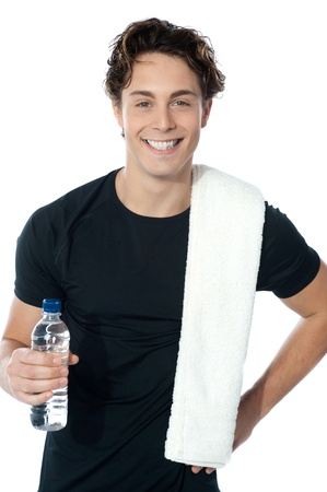 Handsome muscular man with towel holding a bottle of water photo
