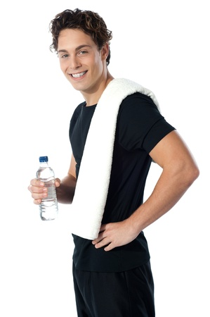 Confident young sporty guy looking at you as he poses with water bottle photo
