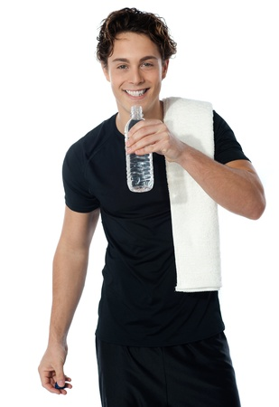 Fit man drinking water with towel on his shoulders isolated on white photo