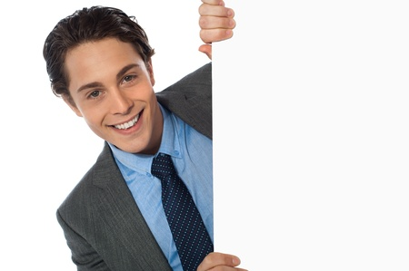 Businessman peeking behind a whiteboard smiling at camera photo