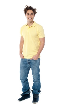 Casual young man standing with hands in pocket against white background Stock Photo - 13217436