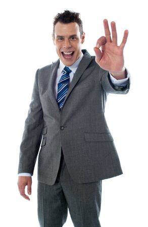 Handsome corporate man gesturing excellent againgt white background photo