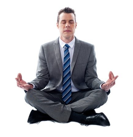 Businessman meditating in lotus position isolated over white background photo