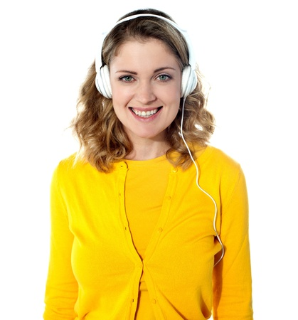 tuned: Smiling young woman listening music in headphones. Isolated on white