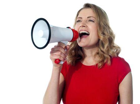 Gorgeous female speaking loudly through megaphone photo