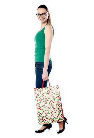 Beautiful shopping woman happy holding shopping bags isolated over white photo