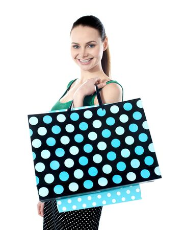 Glamorous smiling teenager shopping  Holding dotted bags photo