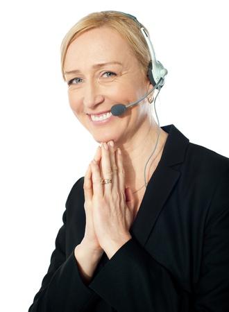 customercare: Senior call centre representative in action, posing with a smile